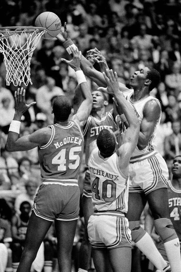 University of Houston's Akeem Abdul Olajuwon, right, North Carolina State's Cozell McQueen (45), and Larry Micheaux (40) of Houston scramble for the tip-in during action in Albuquerque, N.M., April 4, 1983. Photo: Associated Press File Photo