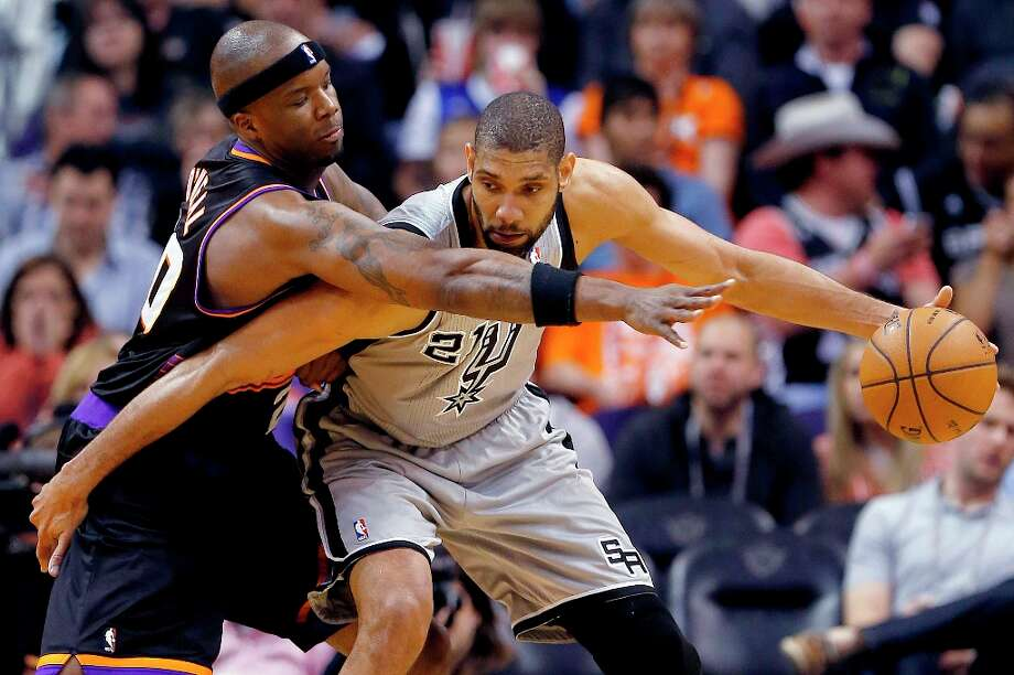The Spurs' Tim Duncan (right) backs down Phoenix Suns' Jermaine O'Neal during the second half Sunday, Feb. 24, 2013, in Phoenix. Photo: Matt York, Associated Press / AP