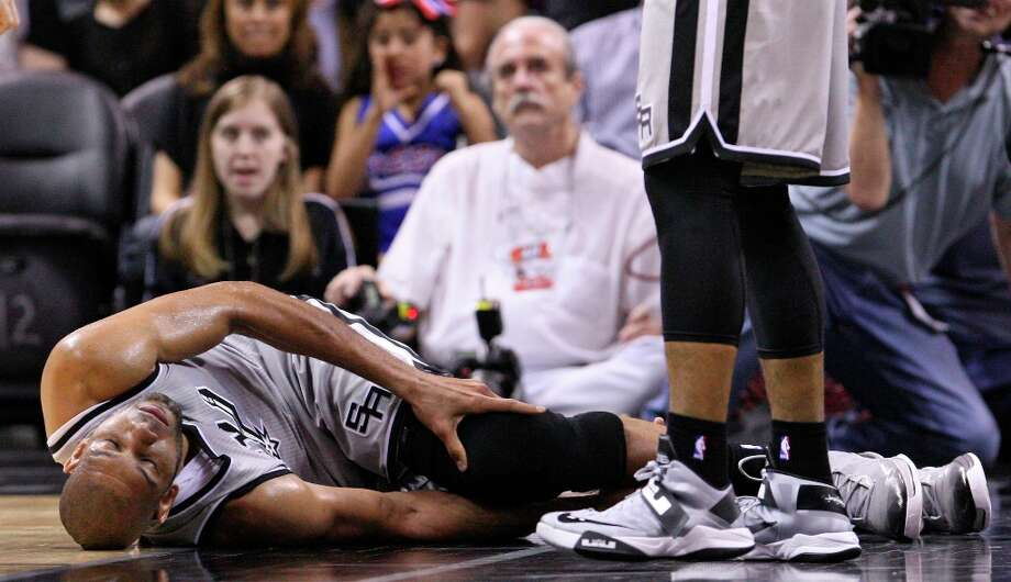 The Spurs' Tim Duncan lies on the floor after being injured on a play during first half action against the Washington Wizards Saturday Feb. 2, 2013 at the AT&T Center. Photo: Edward A. Ornelas, San Antonio Express-News / © 2013 San Antonio Express-News