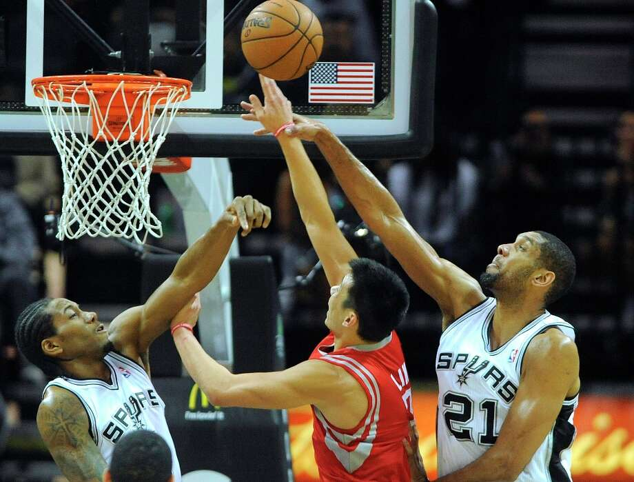 Tim Duncan, right, of the San Antonio Spurs, blocks a shot by Jeremy Lin of the Houston Rockets as Kawhi Leonard of the Spurs also defends during NBA action at the AT&T Center on Friday, Dec. 28, 2012. Photo: Billy Calzada, San Antonio Express-News / SAN ANTONIO EXPRESS-NEWS