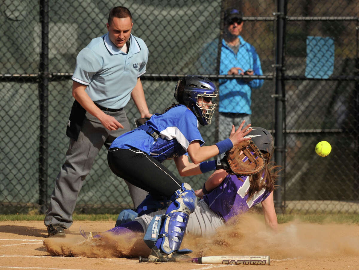 Westhill's Morgan Kurtz slides safely into home beating the tag of Darien catcher Rebecca DeMaio during their game at Darien High School on Monday, April 8, 2013. Westhill beat Darien, 11-9.