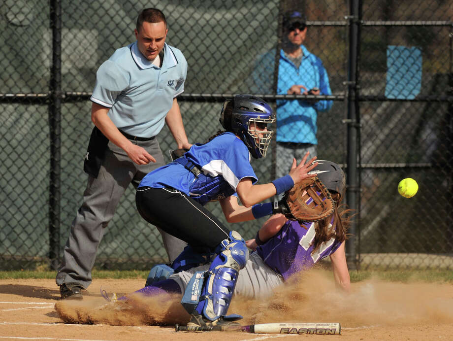 Westhill's Morgan Kurtz slides safely into home beating the tag of Darien catcher Rebecca DeMaio during their game at Darien High School on Monday, April 8, 2013. Westhill beat Darien, 11-9. Photo: Jason Rearick / The (Stamford) Advocate