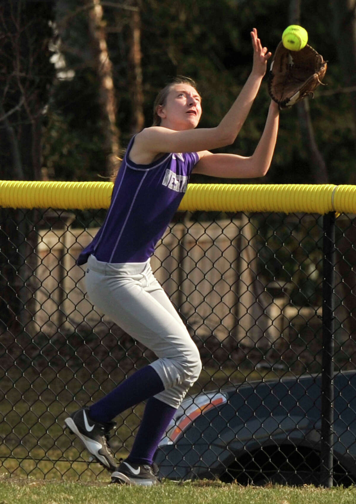 Westhill left fielder Jessica Ruffels makes a catch near the fence during the Viking's game against Darien at Darien High School on Monday, April 8, 2013. Westhill beat Darien, 11-9.