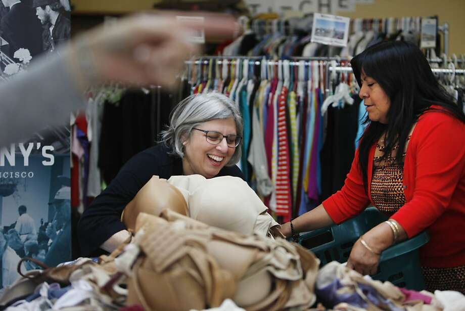 Eileen Hunter (center), one of the founders of Be a Dear and Donate a Brassiere, works with Mariana Chuquin of the St. Anthony Foundation to arrange the donated bras for the women's clothing giveaway. Photo: Lea Suzuki, The Chronicle