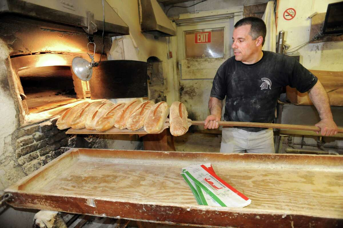 Owner Tony Papa pulls out loaves of baked bread from the brick oven on Friday, March 29, 2013, at Perreca's Bakery in Schenectady, N.Y. (Cindy Schultz / Times Union)
