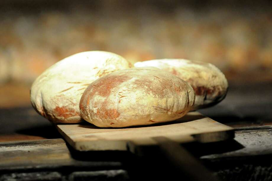 Round loaves of baked bread come out of the brick oven on Friday, March 29, 2013, at Perreca's Bakery in Schenectady, N.Y. (Cindy Schultz / Times Union) Photo: Cindy Schultz / 00021744A