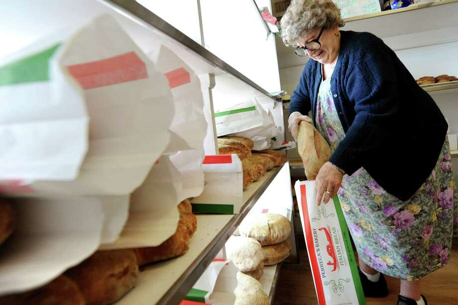 Lilia Perreca Papa, who's parents founded the business, bags fresh baked Italian bread on Tuesday, March 26, 2013, at Perreca's Bakery in Schenectady, N.Y. (Cindy Schultz / Times Union) Photo: Cindy Schultz / 00021744A