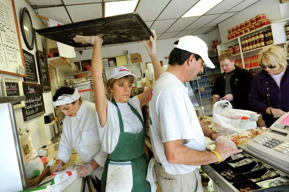 Employee Donna DeGeorgio, center, carries a tray of tomato pizza as Maria Perreca Papa, left, and Richard Nebolini assist customers on Saturday, March 30, 2013, at Perreca's Bakery in Schenectady, N.Y. DeGeorgio, a first cousin to Maria, said she's worked at the bakery since she was 12 years old. (Cindy Schultz / Times Union) Photo: Cindy Schultz / 00021744A
