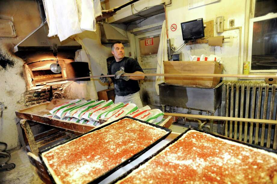 Owner Tony Papa bakes bread and tomato pizza in the brick oven on Friday, March 29, 2013, at Perreca's Bakery in Schenectady, N.Y. (Cindy Schultz / Times Union) Photo: Cindy Schultz / 00021744A