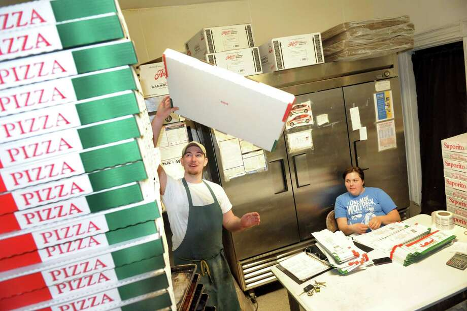 Employees Nelson Jones, left, and Kelly Donnelly work in the back room on Friday, March 29, 2013, at Perreca's Bakery in Schenectady, N.Y. Jones folds and stacks pizza boxes. (Cindy Schultz / Times Union) Photo: Cindy Schultz / 00021744A