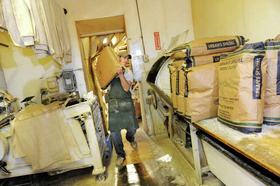 Employee Nelson Jones carries a bag of flour on Thursday, March 14, 2013, at Perreca's Bakery in Schenectady, N.Y. The bakers use about 11 bags of flour during the week and 18 on the weekends. (Cindy Schultz / Times Union) Photo: Cindy Schultz / 00021744A