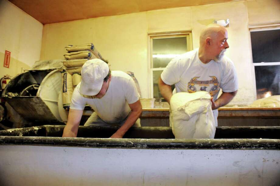 Bakers Tom Bergeron, left, and Jimbo Nellis remove dough from a tub to cut and form into loaves on Friday, March 29, 2013, at Perreca's Bakery in Schenectady, N.Y. (Cindy Schultz / Times Union) Photo: Cindy Schultz / 00021744A
