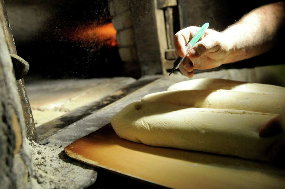 Owner Tony Papa slits the top of loaves before sliding them into the coal-fired brick oven on Friday, March 29, 2013, at Perreca's Bakery in Schenectady, N.Y. (Cindy Schultz / Times Union) Photo: Cindy Schultz / 00021744A