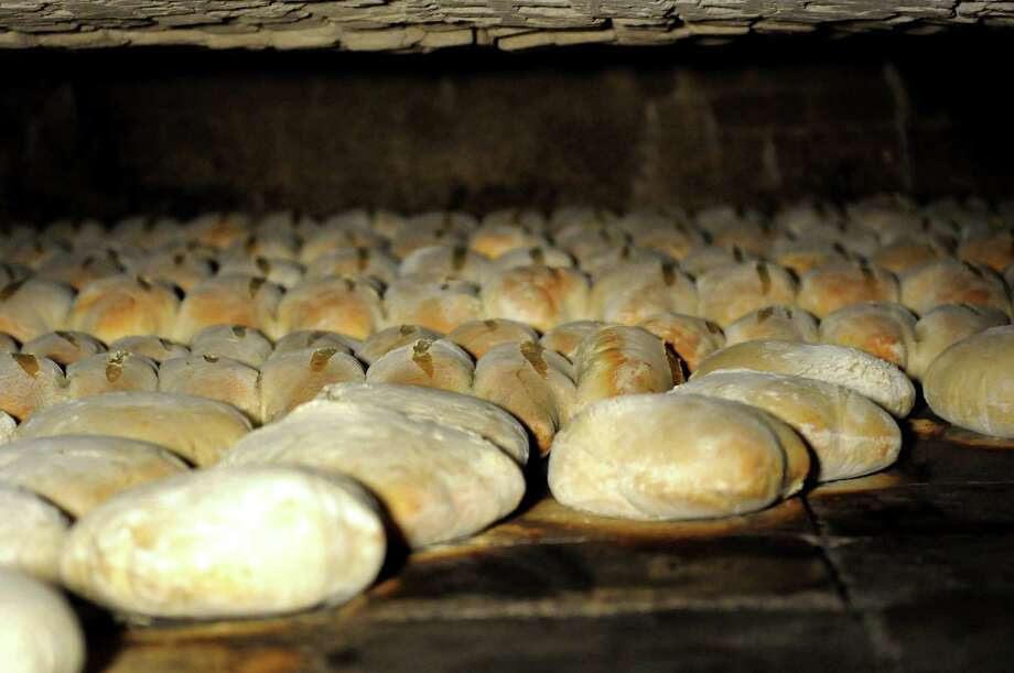 Loaves of bread bake in the low and deep brick oven on Friday, March 29, 2013, at Perreca's Bakery in Schenectady, N.Y. (Cindy Schultz / Times Union) Photo: Cindy Schultz / 00021744A