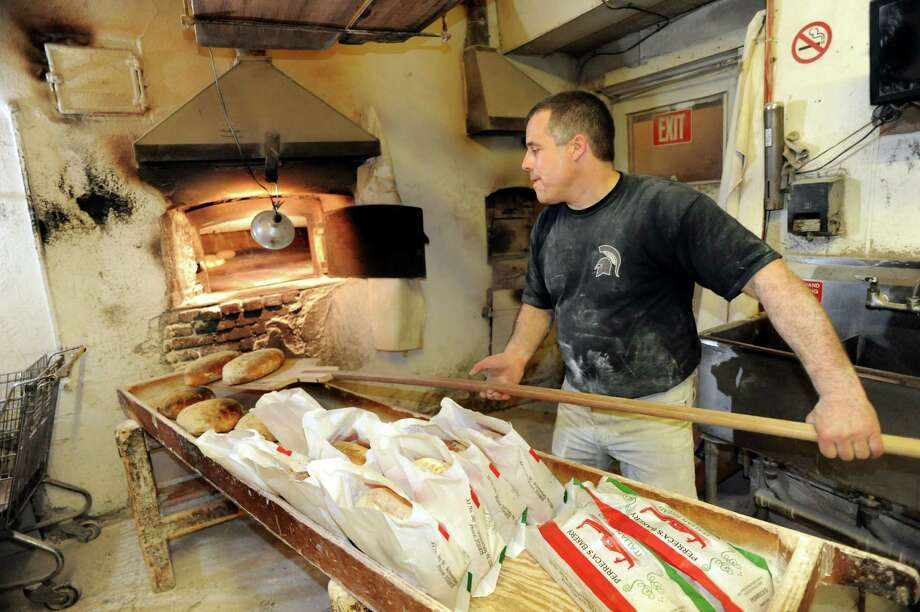 Owner Tony Papa pulls out loaves of baked bread from the brick oven on Friday, March 29, 2013, at Perreca's Bakery in Schenectady, N.Y. (Cindy Schultz / Times Union) Photo: Cindy Schultz / 00021744A