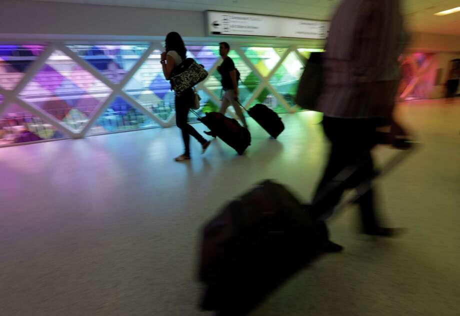 "In this file photo, passengers travel through an airport in Miami. Private researchers, who have analyzed federal data on airline performance, say in a report being released Monday, April 8, 2013, that consumer complaints to the Department of Transportation surged by one-fifth last year even though other measures such as on-time arrivals and mishandled baggage show airlines are doing a better job. ""The way airlines have taken 130-seat airplanes and expanded them to 150 seats to squeeze out more revenue I think is finally catching up with them,"" says Dean Headley, a business professor at Wichita State University, who has co-written the annual report for 23 years. (AP Photo/Lynne Sladky) Photo: Lynne Sladky, Associated Press / Associated Press"