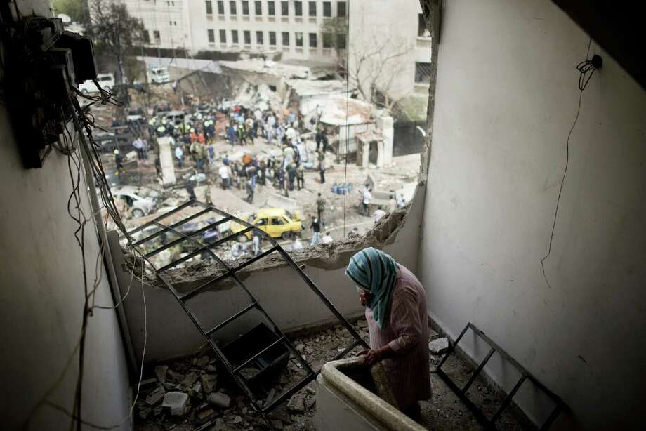 From a hole in her apartment building caused by the car bomb, Jayda Qanna looks out over medical workers and military responders at the scene of the explosion near the Syrian Central Bank in Damascus. Photo: Andrea Bruce / For The New York Times