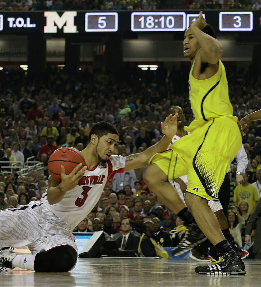Louisville guard Peyton Siva (3) and Michigan guard Trey Burke (3) collide during the first half of the NCAA Final Four tournament college basketball championship game Monday, April 8, 2013, in Atlanta. (AP Photo/Charlie Neibergall) Photo: Charlie Neibergall, Associated Press / AP