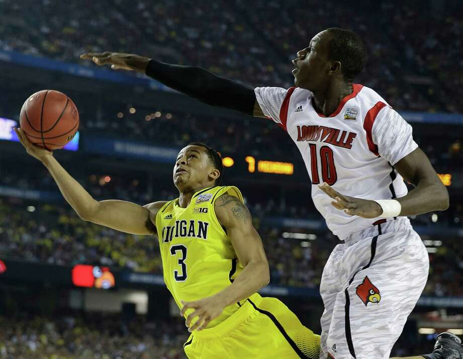 Michigan guard Trey Burke (3) shoots against Louisville center Gorgui Dieng (10) during the first half of the NCAA Final Four tournament college basketball championship game Monday, April 8, 2013, in Atlanta. (AP Photo/David J. Phillip) Photo: David J. Phillip, Associated Press / AP