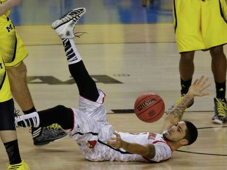 Louisville guard Peyton Siva (3) falls to the court against the Michigan during the first half of the NCAA Final Four tournament college basketball championship game Monday, April 8, 2013, in Atlanta. (AP Photo/Chris O'Meara) Photo: Chris O'Meara, Associated Press / AP