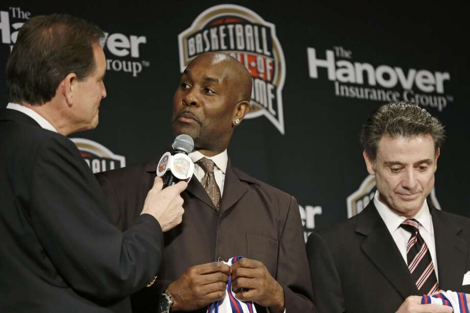 Former NBA player Gary Payton, center, talks with CBS announcer Jim Nantz, left, during the Naismith Memorial Basketball Hall of Fame class announcement, Monday, April 8, 2013, in Atlanta, Georgia. Louisville coach Rick Pitino, right, looks on. (AP Photo/Charlie Neibergall)