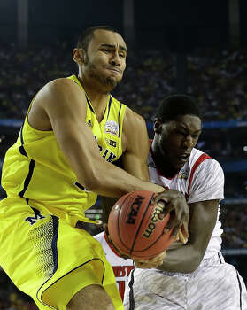 Louisville center Zach Price (25) and Michigan forward Jon Horford (15) vie for a loose ball during the first half of the NCAA Final Four tournament college basketball championship game Monday, April 8, 2013, in Atlanta. (AP Photo/David J. Phillip) Photo: David J. Phillip, Associated Press / AP