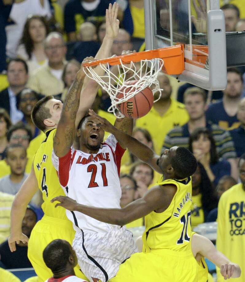 Chane Behanan (21) of the Louisville Cardinals puts in a dunk between the defense of Mitch McGary (4) and Tim Hardaway Jr. (10) of the Michigan Wolverines in the first half of the NCAA Tournament finals at the Georgia Dome in Atlanta, Georgia, Monday, April 8, 2013. (Drew Tarter/MCT) Photo: Drew Tarter, McClatchy-Tribune News Service / MCT
