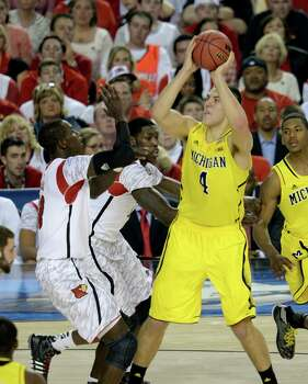 Mitch McGary (4) of the Michigan Wolverines puts up a shot against Gorgui Dieng (10) of the Louisville Cardinals in the first half of the NCAA Tournament finals at the Georgia Dome in Atlanta, Georgia, Monday, April 8, 2013. (Drew Tarter/MCT) Photo: Drew Tarter, McClatchy-Tribune News Service / MCT