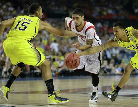 Louisville guard Peyton Siva (3) moves the ball against Michigan guard Trey Burke (3) and Michigan forward Jon Horford (15) during the first half of the NCAA Final Four tournament college basketball championship game Monday, April 8, 2013, in Atlanta. (AP Photo/Charlie Neibergall) Photo: Charlie Neibergall, Associated Press / AP