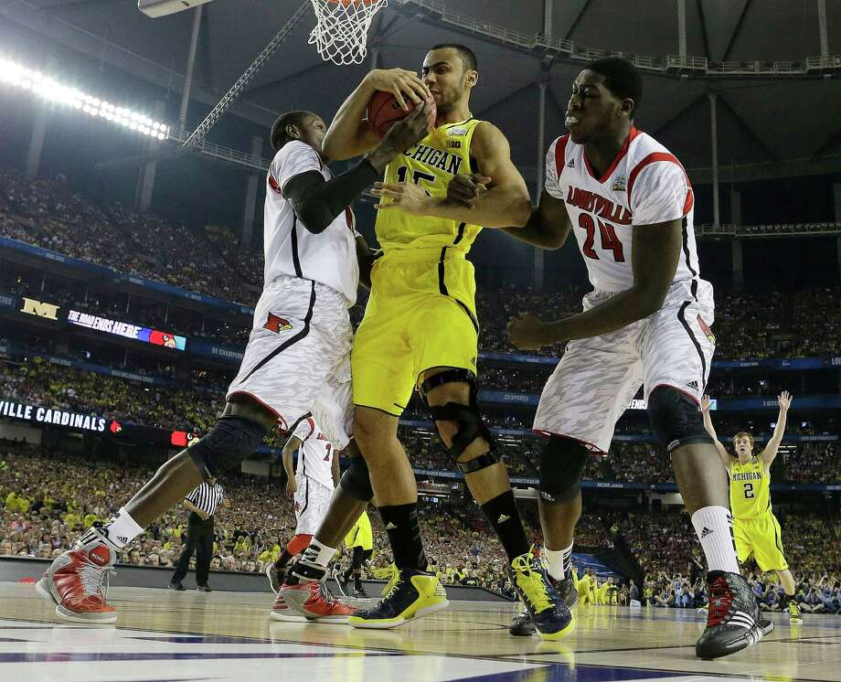 Michigan forward Jon Horford (15) and Louisville center Gorgui Dieng (10) and Louisville forward Montrezl Harrell (24) work for a rebound during the first half of the NCAA Final Four tournament college basketball championship game Monday, April 8, 2013, in Atlanta. (AP Photo/David J. Phillip) Photo: David J. Phillip, Associated Press / AP