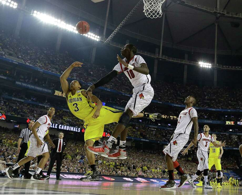 Michigan guard Trey Burke (3) and Louisville center Gorgui Dieng (10) work for a rebound during the first half of the NCAA Final Four tournament college basketball championship game Monday, April 8, 2013, in Atlanta. (AP Photo/David J. Phillip) Photo: David J. Phillip, Associated Press / AP