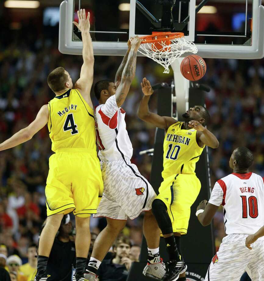 Chane Behanan (21) of the Louisville Cardinals dunks between Mitch McGary (4) and Tim Hardaway Jr. (10) of the Michigan Wolverines during first-half action in the NCAA Tournament finals at the Georgia Dome in Atlanta, Georgia, Monday, April 8, 2013. (Mark Cornelison/Lexington Herald-Leader/MCT) Photo: Mark Cornelison, McClatchy-Tribune News Service / Lexington Herald-Leader
