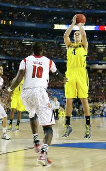 Mitch McGary (4) of the Michigan Wolverines puts up a jumper in the lane in front of Gorgui Dieng (10) of the Louisville Cardinals in the first half of the NCAA Tournament finals at the Georgia Dome in Atlanta, Georgia, Monday, April 8, 2013. (Mark Cornelison/Lexington Herald-Leader/MCT) Photo: Mark Cornelison, McClatchy-Tribune News Service / Lexington Herald-Leader