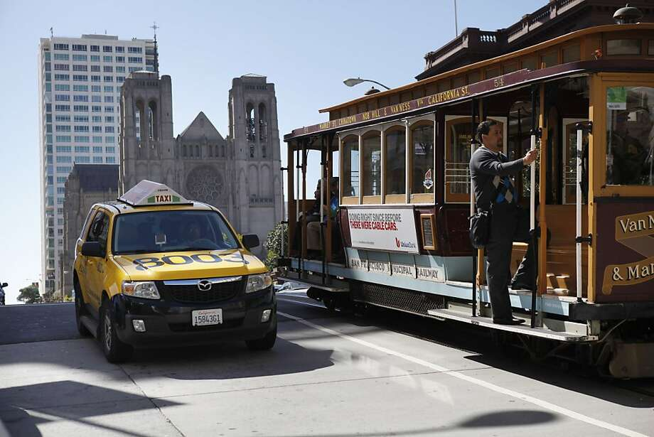 A taxi passes a cable car on Nob Hill. A new report says San Francisco could add 600 to 800 more cabs. Photo: Carlos Avila Gonzalez, The Chronicle