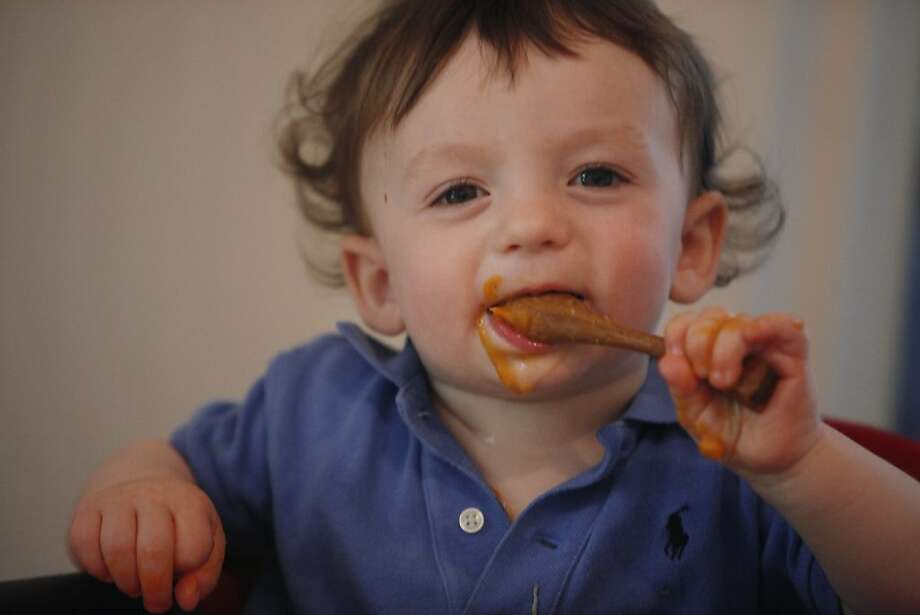 Saul Parker, 13 months, feeds himself bananas and sweet potatoes pureed by his mother. Photo: Lea Suzuki, The Chronicle