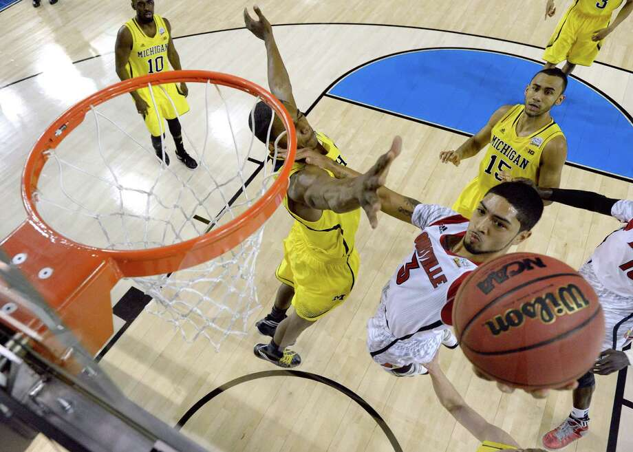ATLANTA, GA - APRIL 08:  Peyton Siva #3 of the Louisville Cardinals drives for a shot attempt in the first half against Glenn Robinson III #1 of the Michigan Wolverines during the 2013 NCAA Men's Final Four Championship at the Georgia Dome on April 8, 2013 in Atlanta, Georgia. Photo: Pool, Getty Images / 2013 Getty Images
