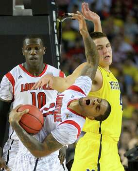 Chane Behanan (21) of the Louisville Cardinals and Mitch McGary (4) of the Michigan Wolverines battle for the ball in the first half of the NCAA Tournament final at the Georgia Dome in Atlanta, Georgia, Monday, April 8, 2013. (Harry E. Walker/MCT) Photo: Harry E. Walker, McClatchy-Tribune News Service / MCT