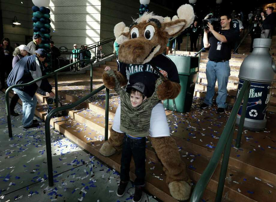 """Moose,"" the Seattle Mariners mascot, greets young fan Jack Baumgart, 7, as the gates of Safeco Field open. Photo: AP"
