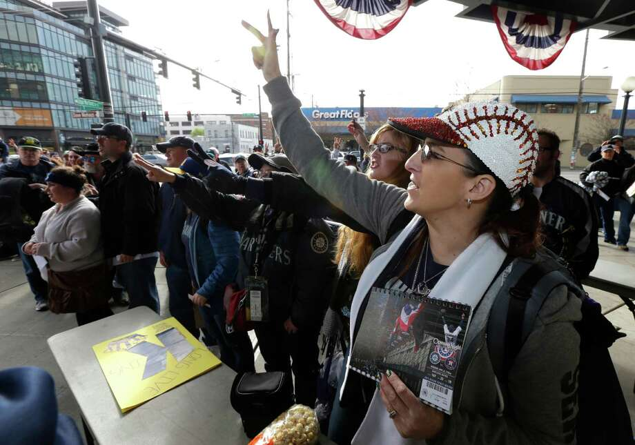 "Seattle Mariners fan Amy Franz, right, wears a baseball ballcap and holds her opening night ticket as she sings ""Take Me Out to the Ballgame,"" while waiting for the gates of Safeco Field to open. Photo: AP"