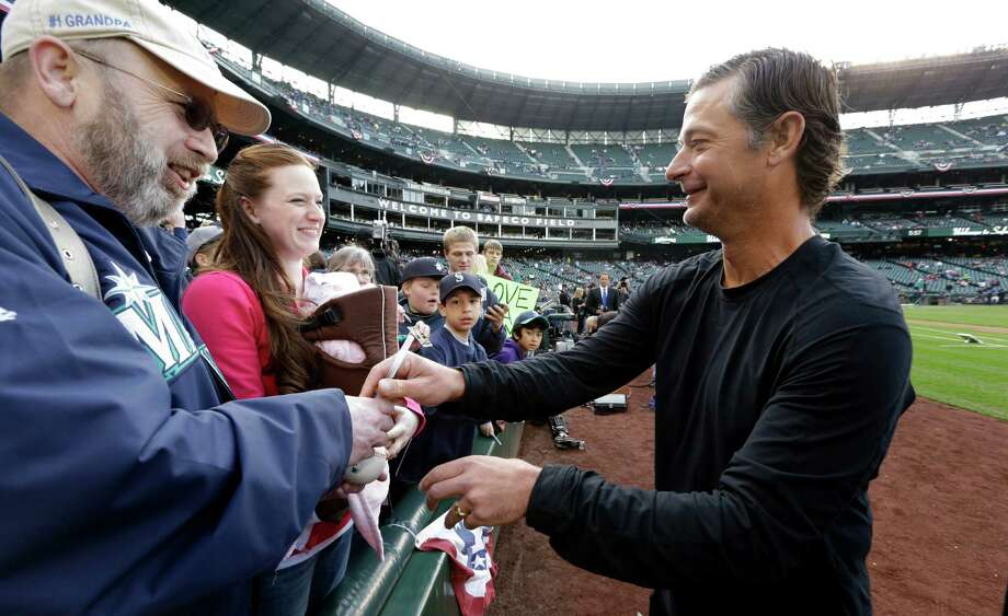 Former Seattle Mariners pitcher Jamie Moyer,  right, signs autographs before throwing out the ceremonial first pitch. Photo: AP