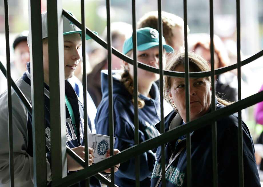 Mariners fans, including J.J. Keller, left, wait for the gates to open at Safeco Field. Photo: AP