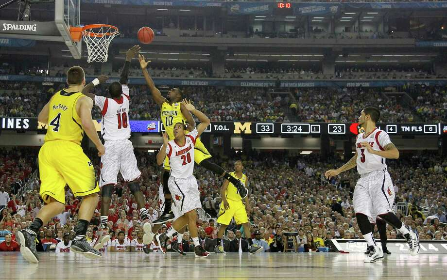 Tim Hardaway Jr. (10) of the Michigan Wolverines puts up a shot in the lane against Gorgui Dieng (10) of the Louisville Cardinals during first-half action in the NCAA Tournament final at the Georgia Dome in Atlanta, Georgia, Monday, April 8, 2013. (Mark Cornelison/Lexington Herald-Leader/MCT) Photo: Mark Cornelison, McClatchy-Tribune News Service / Lexington Herald-Leader