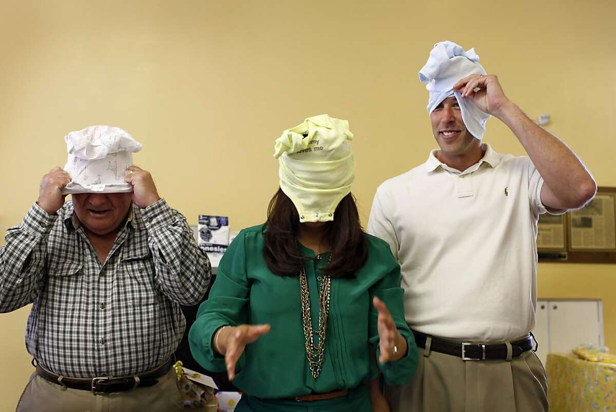 Jennifer Benito-Kowalski, center, and her husband Steve Kowalski compete with Steve's father Mike Kowalski, right, in a speed swaddling and diapering game during their baby shower at Fairbrae Swim and Racquet Club in Sunnyvale, Calif., Saturday, April 6, 2013. After years of trying to conceive a child, a surrogate in India will give birth to their first child in May.