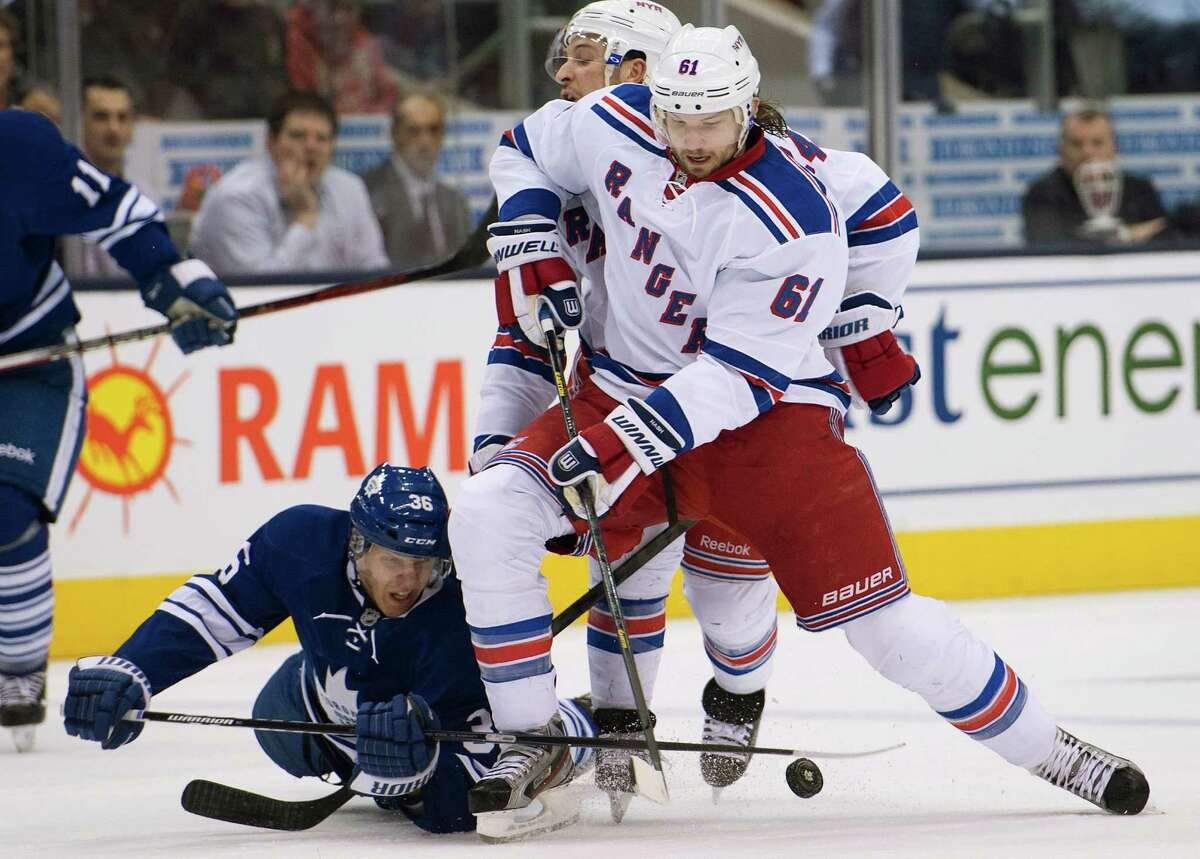 Hitting the ice doesn't prevent the Maple Leafs' Carl Gunnarsson, left, from continuing to dig for the puck against the Rangers' Rick Nash.