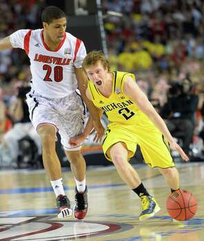 Spike Albrecht (2) of the Michigan Wolverines drives down court against Wayne Blackshear (20) of the Louisville Cardinals in the second half in the NCAA Men's Basketball Championship at the Georgia Dome in Atlanta, Georgia, Monday, April 8, 2013. (Harry E. Walker/MCT) Photo: Harry E. Walker, McClatchy-Tribune News Service / MCT