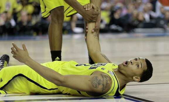 Michigan guard Trey Burke (3) is helped up during the second half of the NCAA Final Four tournament college basketball championship game against Louisville, Monday, April 8, 2013, in Atlanta. (AP Photo/Charlie Neibergall) Photo: Charlie Neibergall, Associated Press / AP