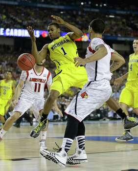 Michigan forward Glenn Robinson III (1) loses the ball as Louisville guard Peyton Siva (3) looks on right during the second half of the NCAA Final Four tournament college basketball championship game Monday, April 8, 2013, in Atlanta. (AP Photo/Charlie Neibergall) Photo: Charlie Neibergall, Associated Press / AP