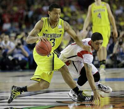 Louisville guard Peyton Siva (3) and Michigan guard Trey Burke (3) work during the second half of the NCAA Final Four tournament college basketball championship game Monday, April 8, 2013, in Atlanta.  (AP Photo/John Bazemore) Photo: John Bazemore, Associated Press / AP