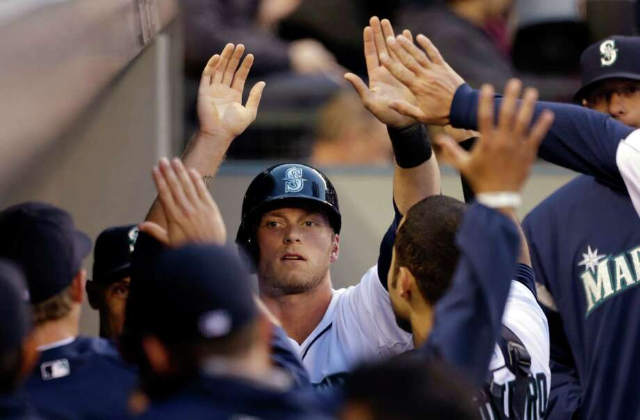 Seattle Mariners' Michael Saunders is congratulated in the dugout after scoring against the Houston Astros. Photo: AP