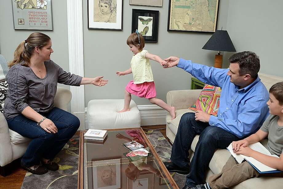 Vale Cervarich and husband Mark play with daughter Lucy as their son, Oscar, watches. Baby Ava died in 2004. Photo: Sean Havey, The Chronicle